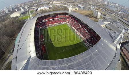MOSCOW, RUSSIA - APR 28, 2014: People watch soccer game in Locomotive sports stadium at evening. Aerial view