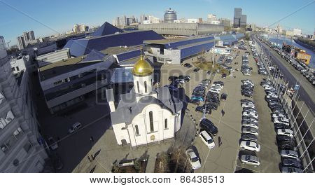 MOSCOW, RUSSIA - MAR 12, 2013: Church and car parking near Expo Center exhibition complex against cityscape at sunny day. Aerial view