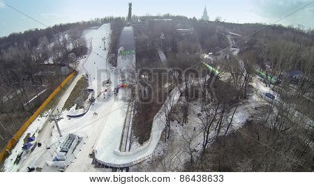 MOSCOW, RUSSIA - MAR 08, 2014: Cableway on snow-covered slope among trees during Speed Descend on Skates competition by Red Bull at sunny day. Aerial view