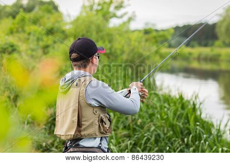 Fisherman on the river bank in sunglasses