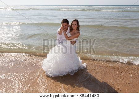 Happy Couple Just Married Relaxing On The Beach Laying In The Ocean