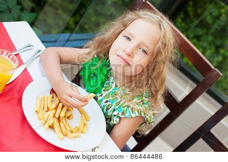 ��¡hild eating potato chips in the cafe. Fast food.
