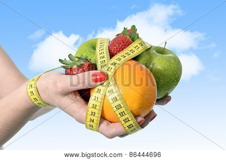Woman Hands With Mix Of Fruit Bond Wrist Wrapped With Measure Tape In Dieting