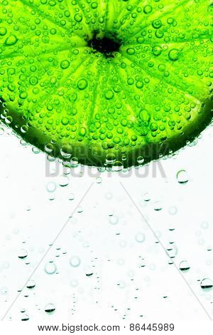 Lime slice in the water with bubbles isolated on white background