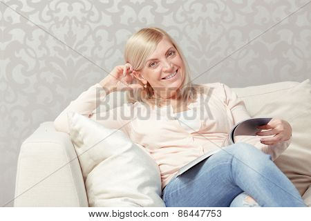 Woman reads magazine at home