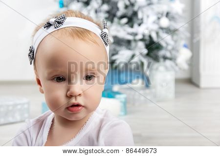 Little Girl In Front Of Christmas Tree Looking Sideways