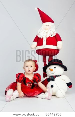 Little Girl Sitting On The Floor Near Christmas Toys