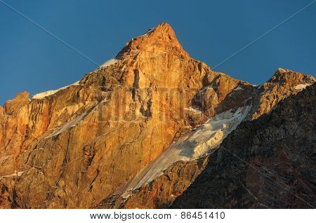 Hight scarlet mountain peak in sunset rays