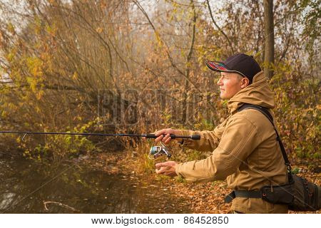 Fisherman on the river bank. Autumn fishing.