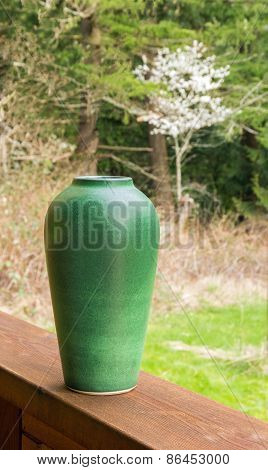 Green Vase Outdoors With Blooming Cherry Tree And Forest