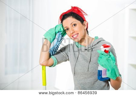 Woman in protective gloves holding a sponge and spray for cleaning