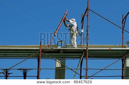 Safety at work. Worker assembles a scaffold