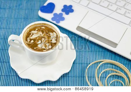 Cup Of Coffee With A White Lap Top