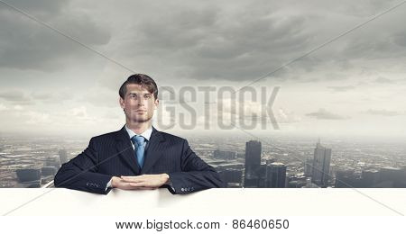 Young businessman holding white blank banner. Place for text