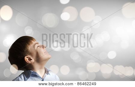 Cute boy with closed eyes against bokeh background