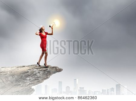 Pretty woman in red dress screaming in megaphone