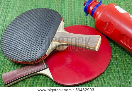 Two Vintage Table Tennis Rackets And A Water Bottle
