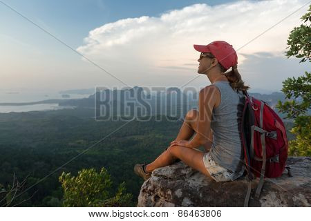 Young lady hiker with backpack sitting on the rock on top of the mountain and enjoying valley view