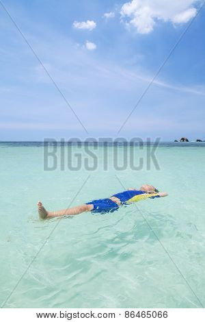 Little Boy Floating On The Beach