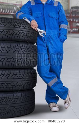 Male Mechanic Lean On Tires In The Garage