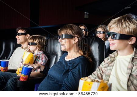 Smiling families with snacks watching 3D movie in cinema theater