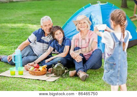 Girl photographing family through smartphone at campsite
