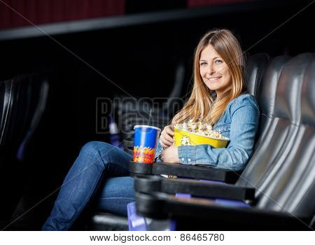 Side view portrait of smiling woman with snacks sitting at cinema theater