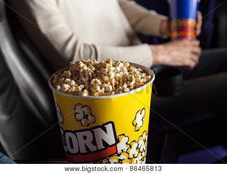 Popcorn bucket at cinema theater with man sitting in background