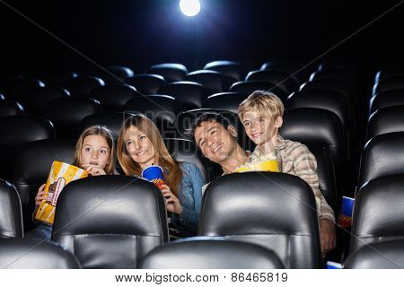 Smiling family of four watching film in movie theater
