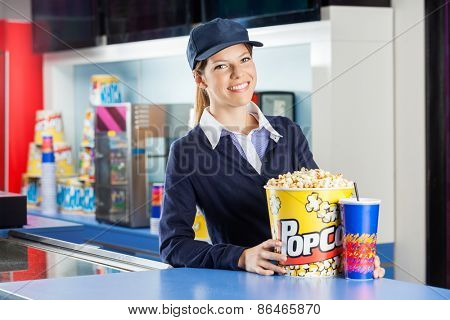 Portrait of confident female worker with popcorn and drink standing at concession stand in cinema