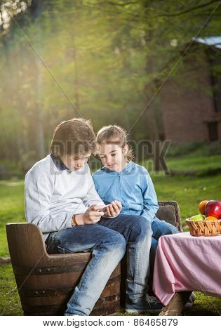 Happy siblings using smartphone while sitting on chairs at campsite