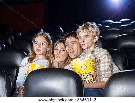 Family of four with popcorn watching movie in cinema theater