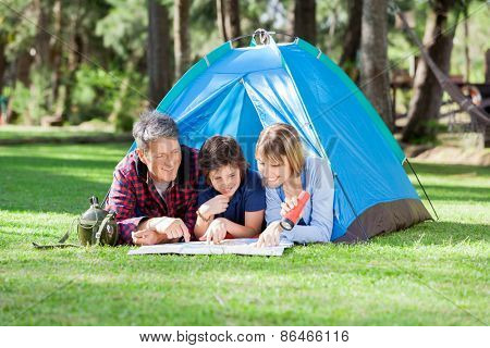 Smiling family reading map at campsite in park