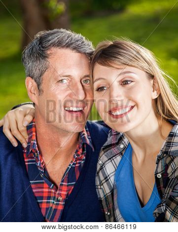 Closeup portrait of happy man with girlfriend at campsite