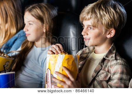 Boy eating popcorn while watching movie with family in cinema theater
