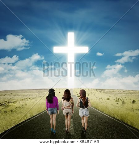 Teenager Girls On The Road With A Cross