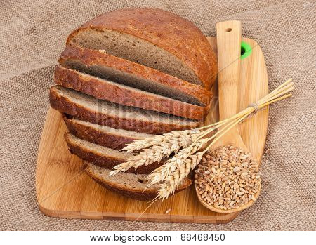 Sliced bread and wheat on sacking