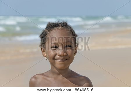 Smiling girl at the beach, six years old