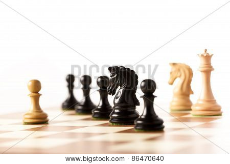 One against all - a white pawn on a chessboard with black chess pieces