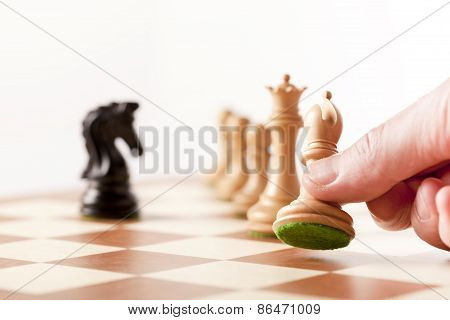 Playing chess - a hand moving chess pieces on a chessboard
