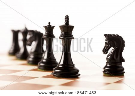 Black chess pieces on a chessboard standing in perspective