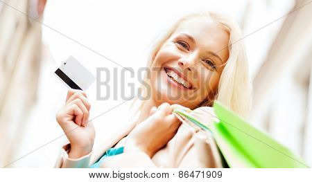 shopping and tourism - beautiful woman with shopping bags and plastic card in ctiy