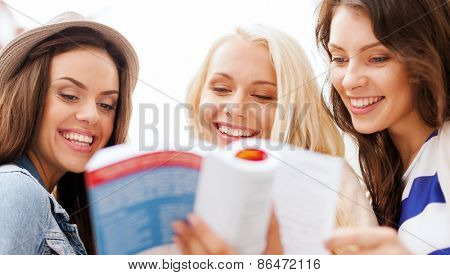 holidays and tourism concept - beautiful girls looking into tourist book in the city