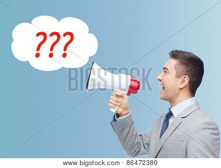 business, people and public announcement concept - happy businessman in suit speaking to megaphone over blue background