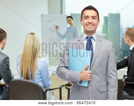 people, meeting and work concept - happy smiling businessman in suit holding open folder over business team in office background