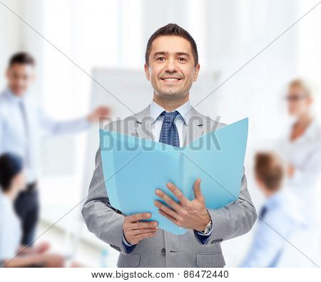 people, finances and paper work concept - happy smiling businessman in suit holding open folder over business team in office background
