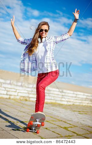 summer holidays, leisure and teenage concept - smiling teenage girl in sunglasses riding skate outside