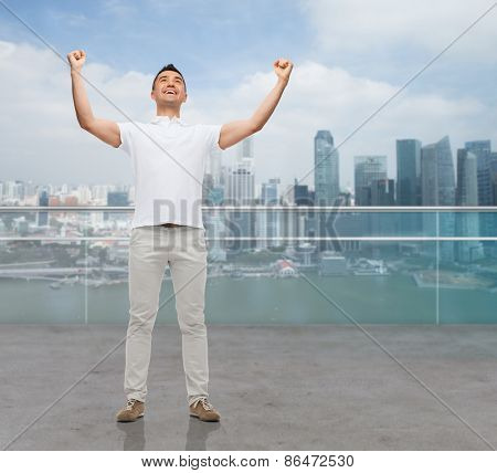 business, travel, tourism, gesture and people concept - happy man with raised hands over city background