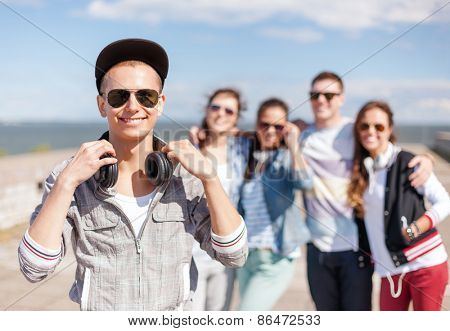 summer holidays and teenage concept - teenage boy in sunglasses, cap and headphones hanging out with friends outside