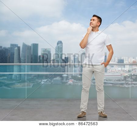 business, travel, tourism and people concept - smiling man with hands in pockets looking up over city background